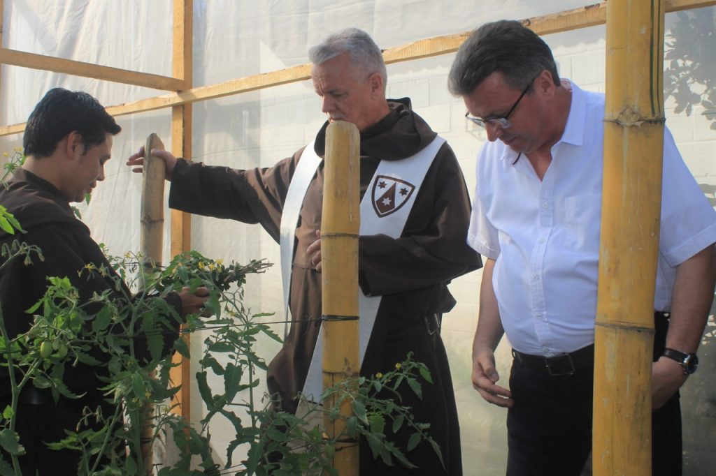 German Consul, Norbert Eichler, joins the Prior Provincial, Fr. William J. Harry, O. Carm., and Br. Benjamin Costante, O. Carm., inspecting the plants inside one of the greenhouses. Br. Benjamin is coordinating programs at the Finca San Elias, and works with the families involved in the greenhouse project. The Finca San Eliás is a project of the Carmelites in El Salvador to fund the ministries of the Order. The principle product is coffee which is sold locally as well as in the United States and Canada.